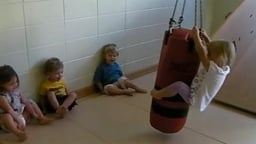 Taking Turns - A teacher helps children share by counting each child's rotations on the swing